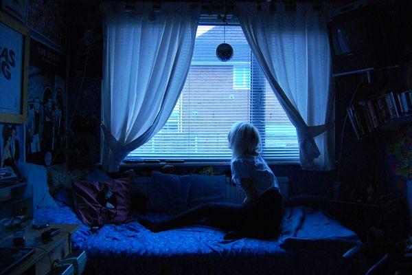 Girl sitting in dark bedroom