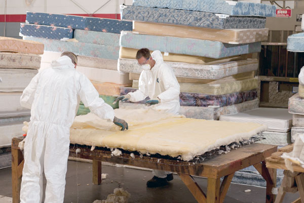 Workers tearing down a mattress to recycle