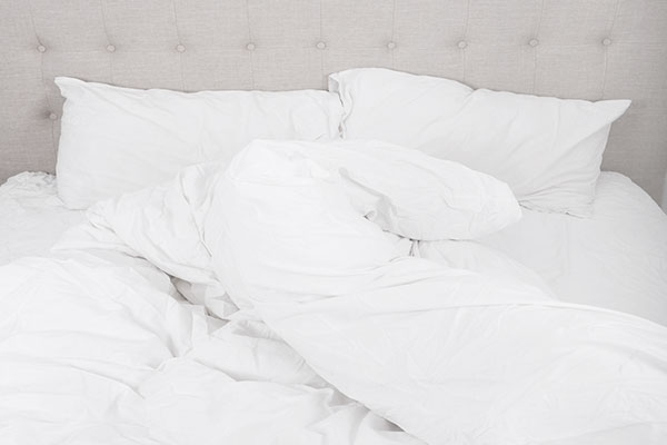 Messy and empty bed with blanket