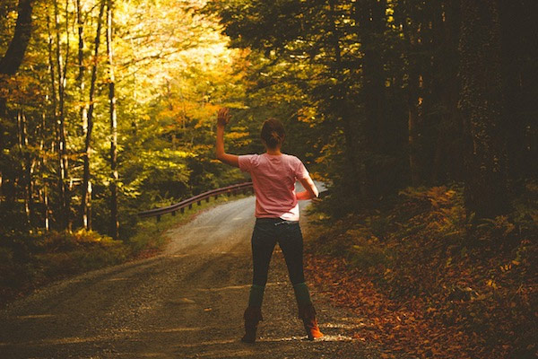 woman waving in road