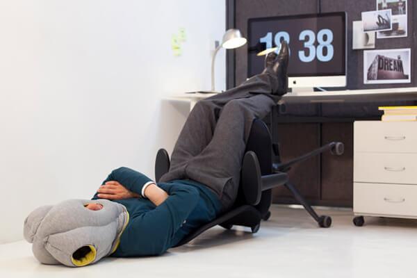 man wearing Ostrich Pillow at work