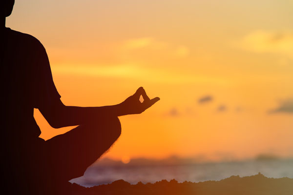 person doing yoga at sunset